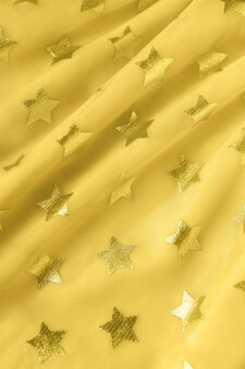 Background, texture of bright yellow mesh fabric with stars. concept trendy color of year 2021 illuminating, festive clothing, feminine, holidays, birthday. for social media, blog, book. copy space.