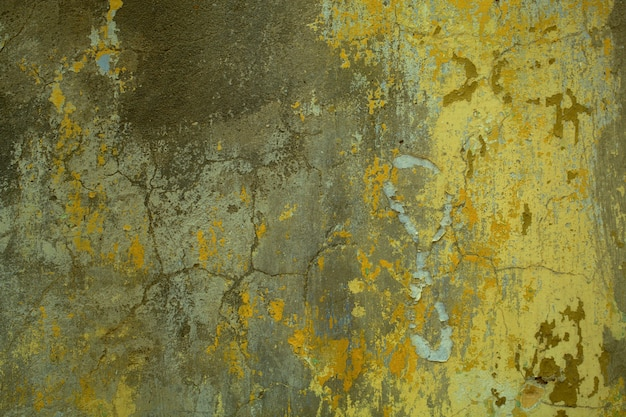 Background texture of cracked concrete wall with remnants of old green paint in a full frame view.