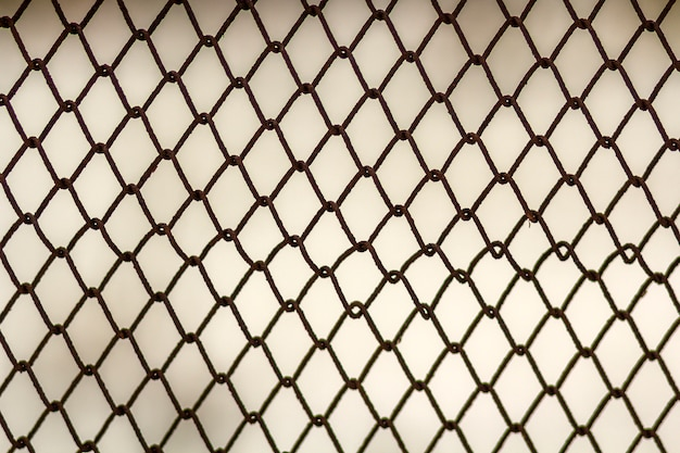 Background and texture for design. abstract chain link fence texture against grungy gray color wall.