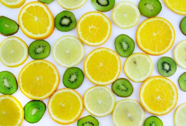 背景のテクスチャ-フルーツミックス:白い背景にレモン、オレンジ、キウイ。閉じる。孤立。
