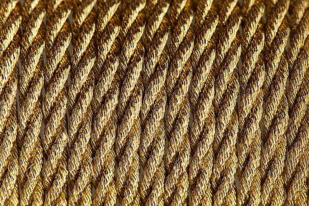 Background texture of gold twisted rope close-up.