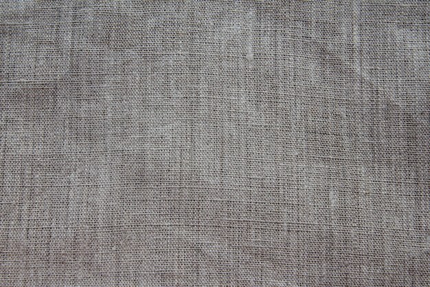 Background and texture of gray linen fabric with close weaving. slightly dented