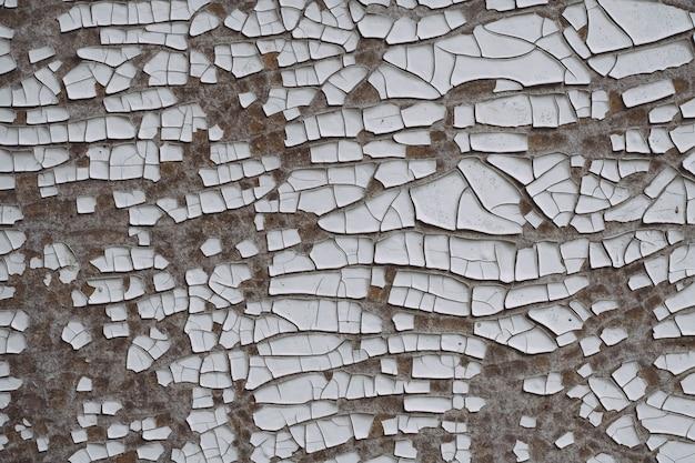背景のテクスチャ。白い古いひびの入ったペンキで灰色の表面。上面図、コピースペース