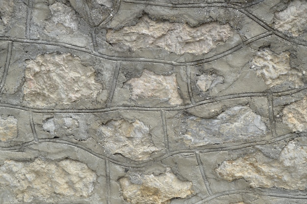 Background, texture of grey stone walls with a concrete solution.