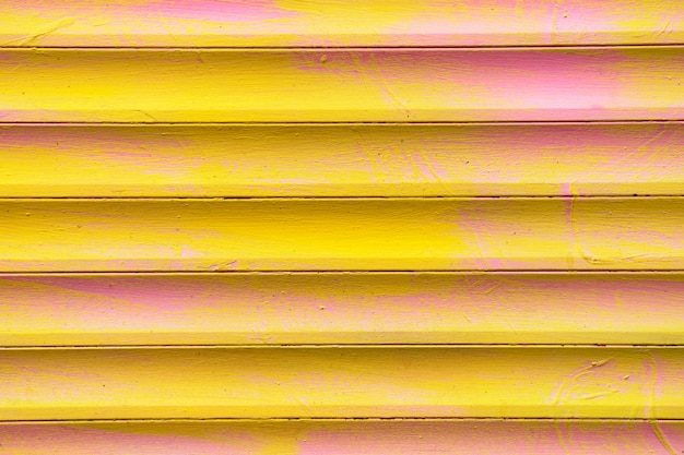 Background and texture of metal gates in yellow and pink colors.