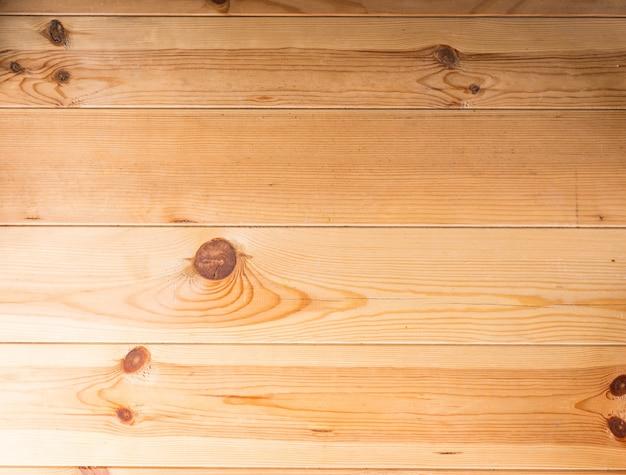 木のテーブルまたは床の背景のテクスチャ、結び目が付いた平行な板、明るい木、フルフレームの独特な木目模様