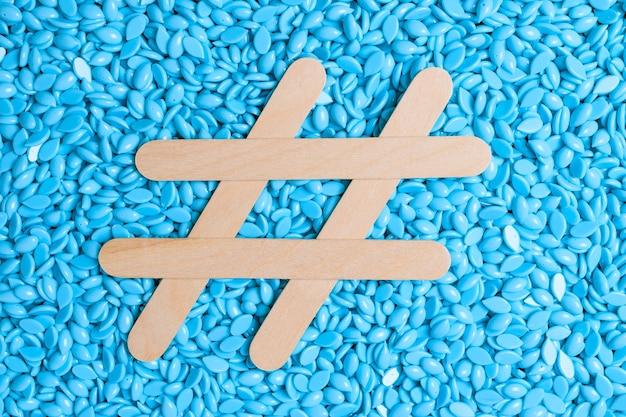 Фоновая текстура синего депиляционного воска со знаком хэштега из деревянных шпателей.