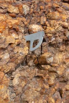 岩肌の背景の質感は、ハンマーで打たれたクライミングフックを備えたコンクリートに似ています。垂直方向の画像。