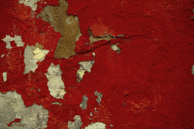 Background texture of old flaking red paint on a wall exposing the concrete below in a full frame view.
