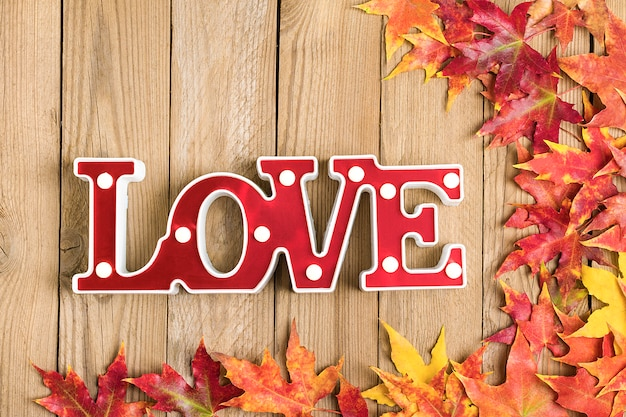 Background texture of old wooden table, yellow autumnal fallen maple leaves, lamp in form of red letters love top view flat lay