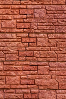 Background texture red stone brick wall with of bricks of different sizes