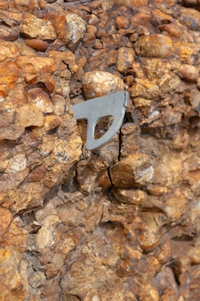 Background texture of rocky surface is similar to concrete with hammered climbing hook. vertical image.