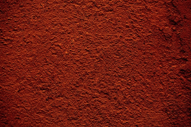 Background texture of a rough finish concrete wall painted in a red brown color in a full frame view.