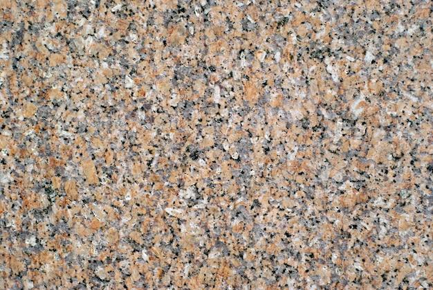 Фон, текстура - поверхность плиты серого гранита с оранжевыми вкраплениями
