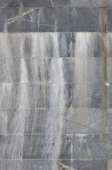 Background texture of a wall from an old gray granite tiles