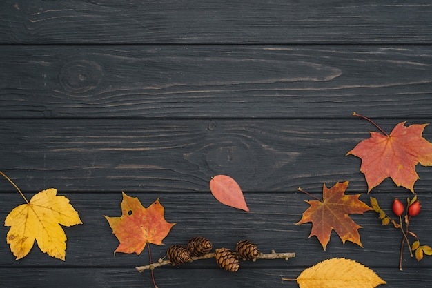 Background texture with old wooden table and yellow autumnal leaves. top view
