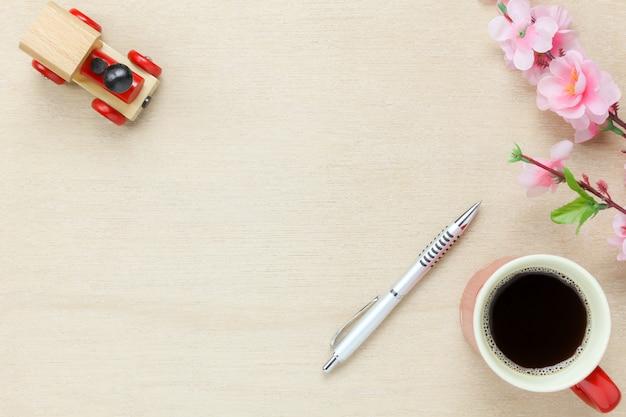 Вид сверху офис офисного стола background.the серебро ручка кофе красивый розовый цветок игрушечный автомобиль на деревянный стол backgtound с копией пространства.