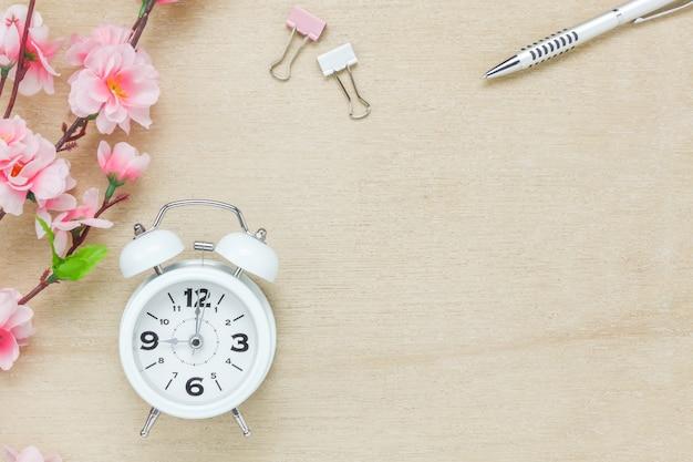 Вид сверху офис офисного стола background.the серебро ручка кофе красивый розовый цветок дерева белые часы на деревянный стол backgtound с копией пространства.