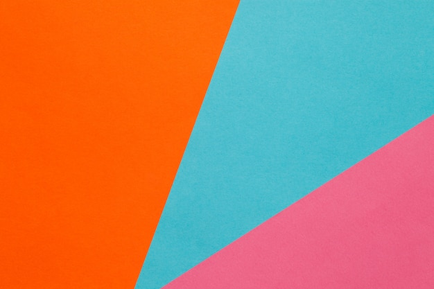 Background of three sheets of colored paper, orange, blue, pink.