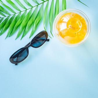 Background tropical leaf palm lemonade refreshing cold ice drink straw hat sunglasses summer vacation
