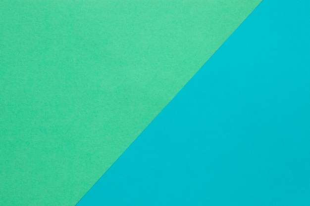 Background of two sheets of colored paper, green and blue.