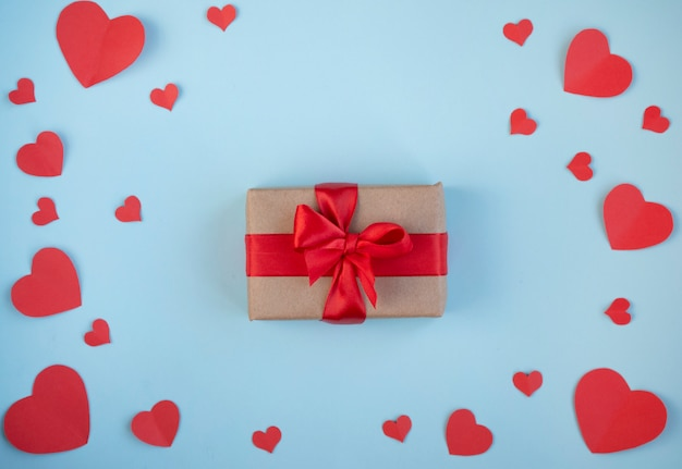 The background of valentine's day.gift in a box with a red ribbon, red hearts, a declaration of love on a light background. the concept of valentine's day. top view, copy space