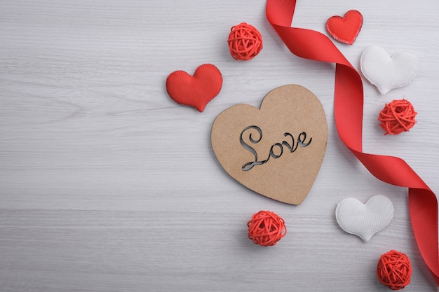 Background for valentine's day greeting card.valentines day concept.red gift ribbons, gifts, hearts on a wooden background. top view.