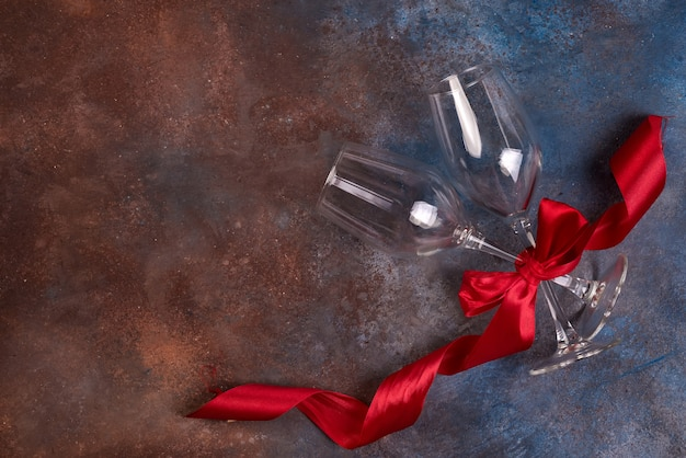Background of valentines day celebration with two glasses and red ribbon