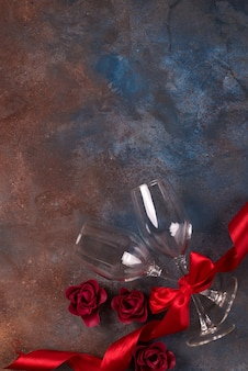 Background of valentines day celebration with two glasses, roses and red ribbon