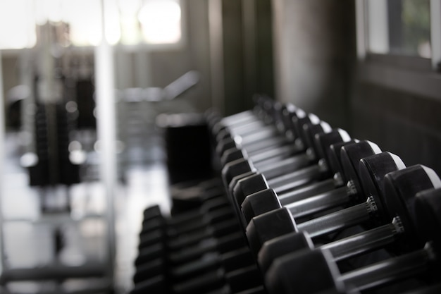 Background view back and white equipment dumbbells on rack in the gym sport center