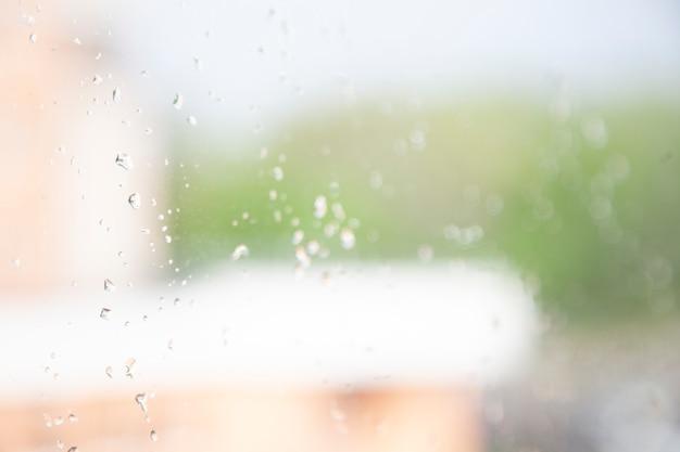Фон, вид из окна в мягком фокусе на оранжевое здание и деревья, капли дождя на стекле. печальный, дождливый день ..