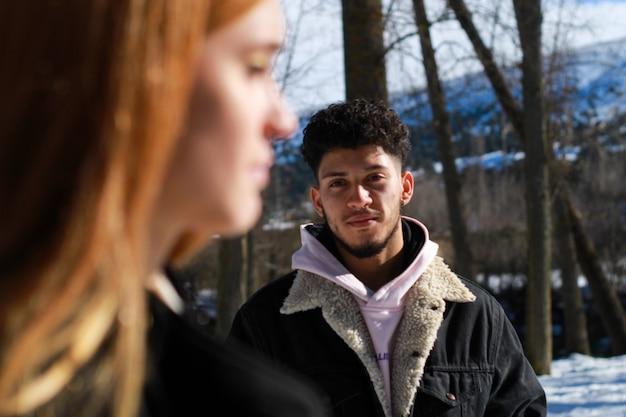 冬の金髪白人少女の顔の若いラテン系男性の背景図