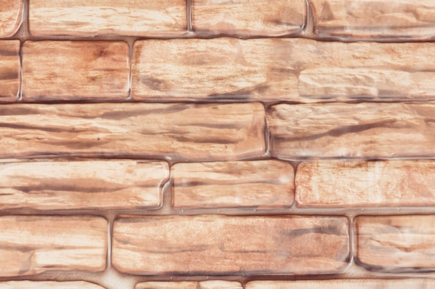Background wall of large bricks of red color close-up.