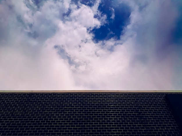 Background of a wall with dark blue brick and sky with clouds.
