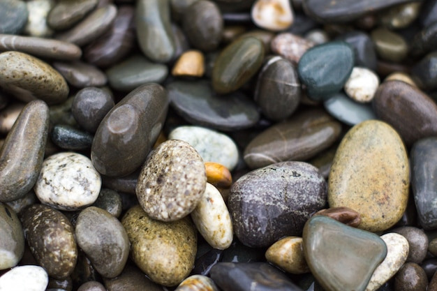 Background of wet sea pebbles by the sea