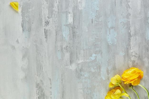 黄色い花を持つ背景の白灰色のコンクリートのテクスチャー。