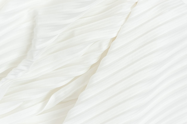 Background of white pleated fabric located diagonally. plisse cloth texture of white female skirt closeup.