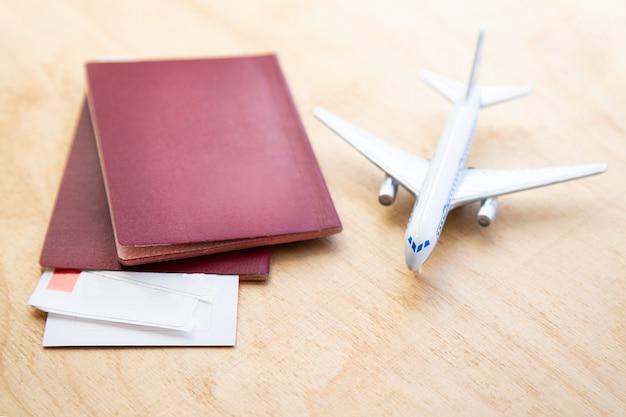 模型飛行機の背景と木製のテーブルの航空券とパスポートの横に横たわっています...