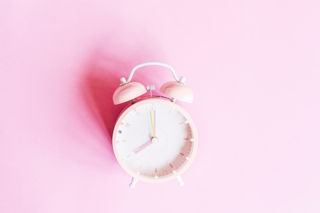Background with alarm clock on pink paper. place for text. top view. flat lay