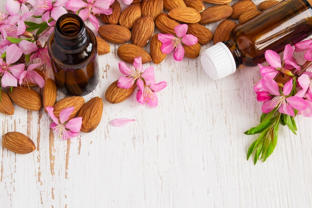 Background with almond oil, almonds and flowers