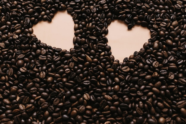 Background with array of dry coffee beans with two heart shapes.