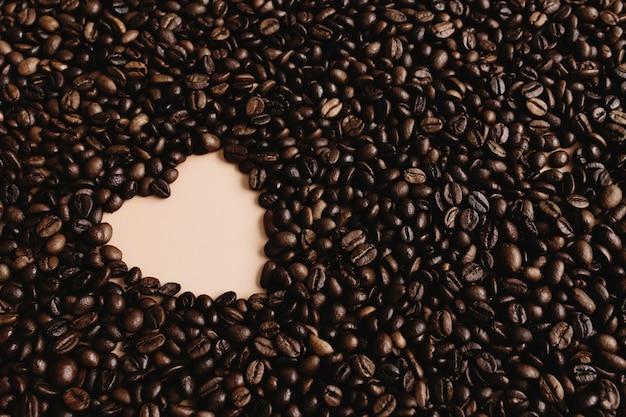 심장 모양으로 건조 커피 콩의 배열과 배경. 베이지.