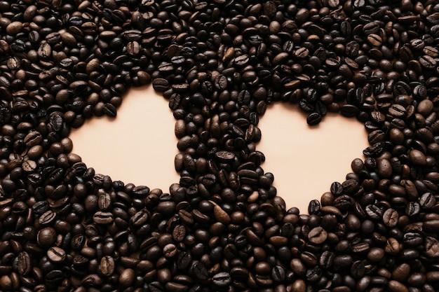 Фон с массивом сухих кофейных зерен с двумя сердечками.