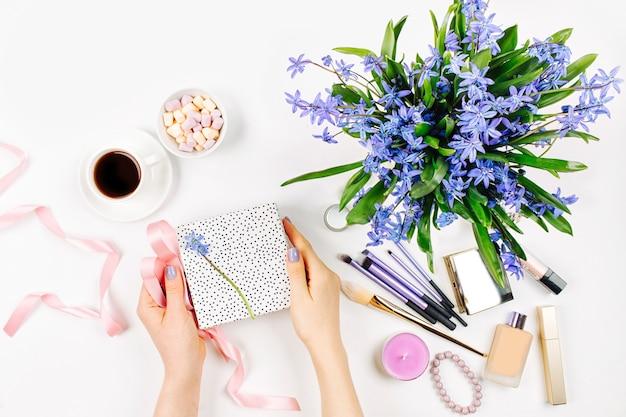 Фон с синим весенним букетом кофейная чашка, конфеты и косметические аксессуары
