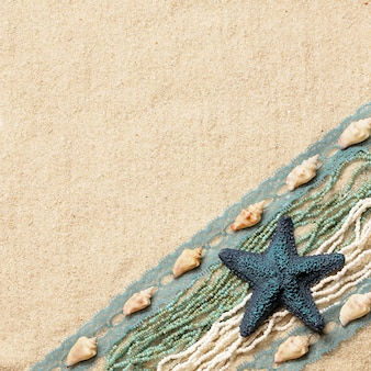 Background with a blue starfish, seashells, ribbons and beads