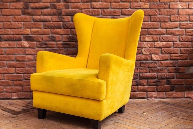 レンガの壁と黄色のアームチェアの背景。横の写真