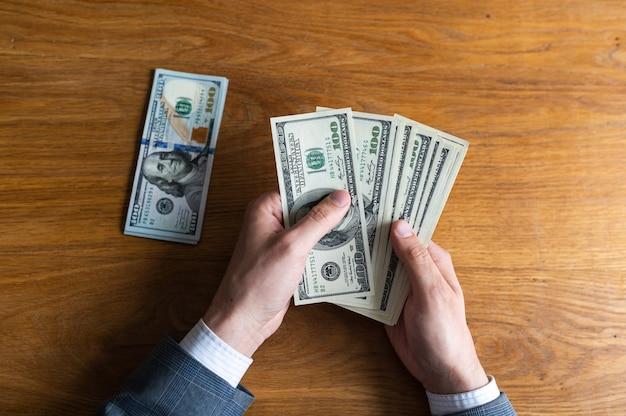 Фон с наличными деньгами, американские стодолларовые банкноты, ноутбук, телефон и документы, плоский вид сверху