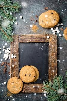 黒板、自家製チョコレートチップクッキー、マシュマロの背景。フラットレイ、スペース