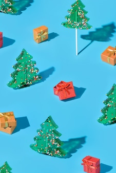 Фон с рождественскими елками и подарочными коробками на синем фоне. встреча нового года и рождества. минималистичная композиция с леденцами и подарками.