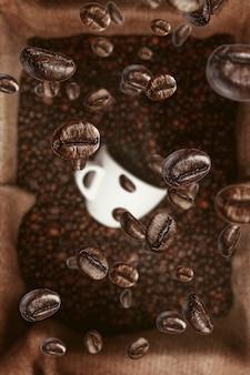 Фон с кофейными зернами, падающими на чашку кофе